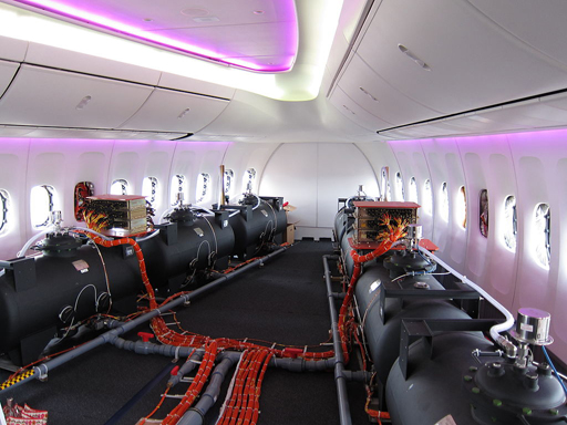 Olivier Cleynen from Wikipedia: Ballast barrels in a prototype Boeing 747. Photographs of flight test barrels are sometimes said to show chemtrail planes.