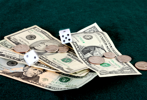 American currency and coins with rolling dice on a green gaming table